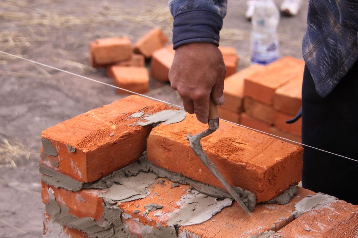 Muratore in a elmetto protettivo costruzione mattone